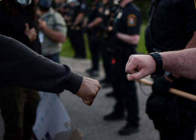 A protester and police officer bump fists during a peaceful protest in Flint Township of the death of George Floyd.